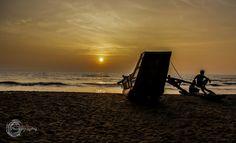 Couple of men sitting on a boat during sunset in Wadduwa Beach, Sri Lanka