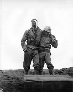 """Wounded Marine, Iwo Jima, 20 February 1945.  Photo caption: """"Iwo Jima, February 20, 1945. Buddy to the Rescue: A wounded Marine gets a lift from a comrade after he was wounded by Japanese mortar fire on Iwo. Casualties were treated at front line aid stations and evacuated to rear bases for further medical attention.""""   From the Photograph Collection at the Marine Corps Archives and Special Collections   OFFICIAL USMC PHOTOGRAPH"""