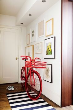Red bicycle in entryway of home with gallery wall and white walls // the home of fashion designer Peter Som