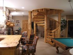Custom log spiral staircase in a modern home, with custom slab bar and beautiful mantel