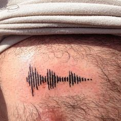 "My son recorded me saying ""I love you"" with sound waves.  He suprised me with this tattooed on his chest."