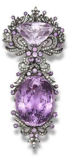 # A kunzite and diamond brooch Designed as a detachable brooch, which can be worn as two separate pendants, set with an oval mixed-cut and a triangular mixed-cut kunzite, within a foliate surround set with circular-cut kunzites and brilliant-cut diamonds, mounted in 18k blackened gold, the oval kunzite estimated to weigh approx. 100.00 carats, the triangular kunzite estimated to weigh approx. 25.00 carats, the diamonds estimated to weigh approx. 1.36 carats in total, brooch length 8.9cm