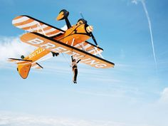 """Most people dance with their feet on the ground. The Breitling Wingwalkers acrobats perform their synchronized ballet in mid-air and in full flight, perched on the upper wing of a plane. A truly breathtaking sight.  The spiritual heirs of the famous """"barnstormers"""", the teams of pilots and stuntmen who performed during the period between the two world wars, the Breitling Wingwalkers are equipped with 1940s open-cockpit Boeing Stearman biplanes – complete with the beautiful signature sound of…"""