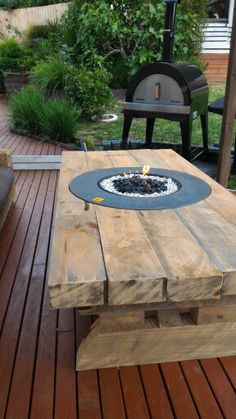 Diy Rustic table made from railway sleepers with fire pit in the centre.