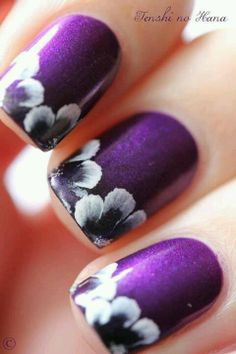 Purple nails with flowers now if only my daughter would stop biting her nails
