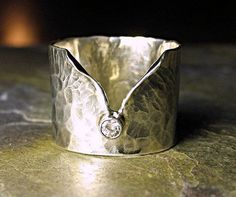 Ice Whisper - A gorgeous top quality diamond (VVS or better) rests on a wide band ring of hammered sterling silver. Also available with ruby, sapphire or emerald..