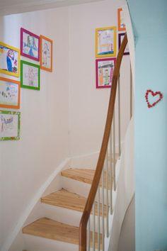 Barnetegninger i fargerike rammer på hvit vegg - kaos og helhet samtidig!