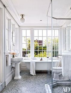 The master bath is equipped with a Duravit pedestal sink and a ceiling light by Thomas O'Brien from Circa Lighting.