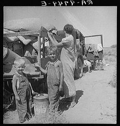 """Part of an impoverished family of nine on a New Mexico highway. Depression refugees from Iowa. Left Iowa in 1932 because of father's ill health. Father an auto mechanic laborer, painter by trade, tubercular. Family has been on relief in Arizona but refused entry on relief roles in Iowa to which state they wish to return. Nine children including a sick four-month-old baby. No money at all. About to sell their belongings and trailer for money to buy food. """"We don't want to go where we'll be a nuisance to anybody."""" Children of migrant workers typically had no way to attend school. By the end of 1930 some 3 million children had abandoned school. Thousands of schools had closed or were operating on reduced hours. At least 200,000 children took to the roads on their own. Summer 1936. Photographer: Dorothea Lange."""