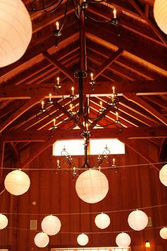 Hanging paper lanterns mixed between chandeliers in a rustic setting. Photo by Kate Harrison