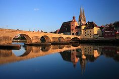"""Old stone bridge """"Steinerne Brücke"""" spans the Danube with 16 arches and is part of the World Heritage of Regensburg Germany"""