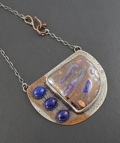 A handmade sterling silver bezel is set with a beautiful boulder opal stone. 3 dark blue lapis stones are added to the left side. The sterling silver has been roll printed for added detail. A copper strip, also roll printed in a contrasting print, is soldered under the lapis stones. The entire piece has been oxidized to bring out the detail. The pendant measures approx 2 1/2 long by 1 7/8 high and hangs from an 18 sterling silver chain with a handmade copper clasp that hooks in fron...