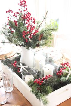 Coastal Christmas centerpiece: white painted wood crate with greenery, berries and hurricanes. http://kristyseibert.com/blog/2014/12/starfish-cottage-kitchen-christmas-tour-2014.html