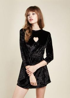 This long sleeve, black velvet mini-dress features a heart cut out. - 50% polyester - 50% spandex - Rachel and Page are wearing size (S) - Machine wash in cold water - Do not bleach or use harsh chemi