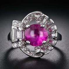 A gemmy, luscious hot pinkish-red gumdrop, weighing 2.40 carats, is served up on the half shell in this chic and sumptuous jewel, dating from the late 1930's. The bright and glowing cabochon ruby is embraced on all sides with sparkling baguette and round diamonds, artfully arrayed in the form of a stylized scallop shell.