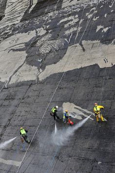 A mural has been done on the side of this dam by washing away layers of dirt.