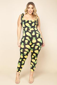 A plus size sleeveless bodycon jumpsuit with a flat neckline. Features knotted shoulder straps and a cinched waist. Pineapple print allover.