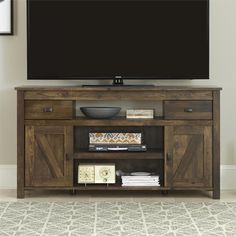 Inspired by the weathered look of an old barn, this TV stand has various open compartments and closed storage to keep media essentials organized. Holds up to a 60 inch flat panel TV.  The stand requires assembly upon delivery and ships in two boxes. https://emfurn.com
