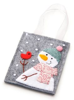 This handmade snowman ornament features a snowman holding a little red bird. Jenn Maruska