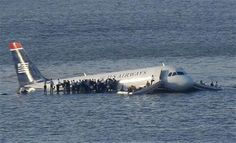 Passengers stand on the wings of a U.S. Airways plane after it landed in the Hudson River in New York, January 15, 2009.  REUTERS/Brendan McDermid