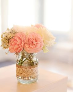 how lovely is this? an empty mayonnaise jar, burlap, white lace, and the prettiest flowers to adorn your guest tables!