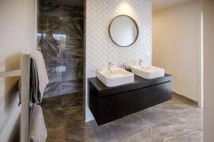 Brodie & Niki Retallick's ensuite with grey floor tiles, double wall hung vanity and herringbone subway tiled splashback. #ensuite #house #interiordesign #bathroom #herringbone #brodieretallick #generationhomes