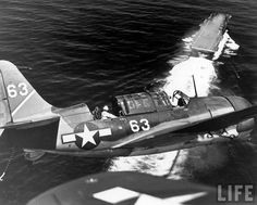 U.S. Navy SB2C Helldiver scout plane circling above an aircraft carrier prior to landing,1944.