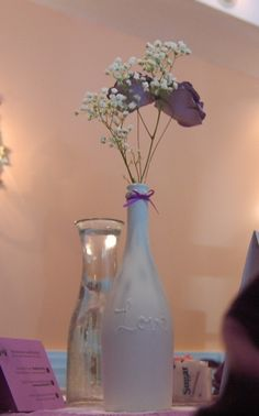 Wedding Centerpiece ... DIY ... wine bottle spray painted white ... raised letters are puff paint under white paint ... handmade paper roses ... fresh baby's breath