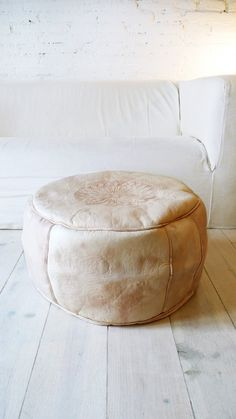 Leather natural colored Pouf, with a design on the top. Made by artisans in Morocco..: Color: Natural.: Material: Goat-skin leather.: Size: Ø 42cm x 25cm hight /// Ø 16,5in x 9,5in hight ( /-).: Handmade in MoroccoThe filling is done by opening a zipper underneath.These poufs are sent without filling for comfort. Unstuffed pouffes are smaller, lighter.If you would prefer your pouf pre-stuffed, please convo me. Shipping weight of pre-stuffed poufs will d...