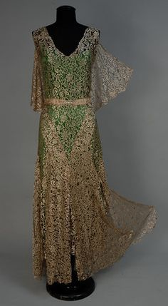 GOLD LACE EVENING GOWN, 1930s Sleeveless allover lace with V-neck and deep V-back, back shawl collar. Skirt has six attached inverted scallop panels for fullness sewn along one side to dress and extending 7 inches below skirt hem.