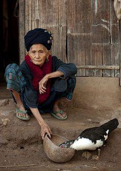 Elderly Yao woman feeding her duck in Laos