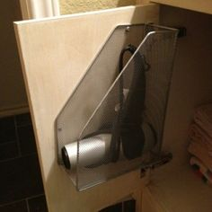 Metal magazine holder turned on its side and attached to the inside of the bathroom cabinet door to store your blow dryer.