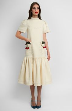 Low-waist breast-yoke textured stretchy cotton dress. Band collar with cotton lace trim. Patch pockets with fixed decorative cherries. Puckered sleeves. Hidden back zip closure.