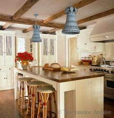 Bunny Williams ~ A pair of blue/grey pendant lights above the large wood-topped kitchen island