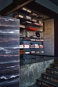 Quelques marches permettent, du salon, de rejoindre la salle à manger puis les parties privées. L'escalier comme la bibliothèque, en métal et marbre, ont été dessinés par Dimorestudio. Au premier plan, on aperçoit l'un des panneaux de la paroi mobile qui sépare l'entrée du salon. Il est tapissé de papier peint Travertine (Fromental).