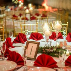 Real Weddings - In Bliss Weddings  Each table was reminiscent of Christmas with red folded napkins, evergreens, and white votive candles in clear glass pedestal candle holders. Table numbers were placed inside of gold picture frames.