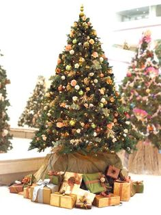 """Midwest Living: Elements of Nature:  The """"Bounty of the Midwest"""" tree is decorated with earth-tone colors and orange silk roses. To add to the natural theme, the editors used wheat bundles, dried hydrangea, and magnolia evenly throughout the tree."""