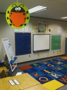 My classroom meeting area and smart board.  100 chart and pocket chart on each side for easy access, class promise above. 1st grade