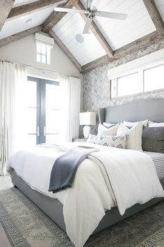 The gray, white, and navy tones in this master bedroom are breathtaking! We especially like the wood accent wall and exposed ceiling beams.