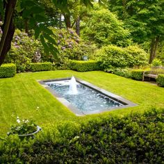 The formal gardens reflecting pool with spouting water is framed by Wintergem boxwoods and lead urns.