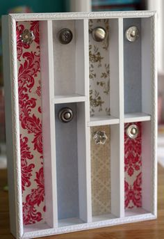 Take an Old or New silverware holder, Add your liking of decorative paper behind for the backsplash, Pick out cute nobs for the jewelry to hang from. Paint it any color along with adding a nice trim or border around the actual holder.