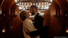 Dim lit couple photography in front of hanging light fixture, romantic wedding photos