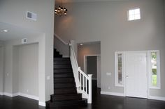 This stairway has undergone a complete facelift, as seen on HGTV's Flip or Flop. Dingy green walls were covered with a clean neutral tone and dark wood replaced an ugly beige carpet for a fresh contemporary look.