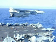 F-14 Tomcat flying past an aircraft carrier.