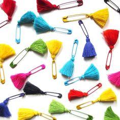 Alfileres de gancho pintados con borlas de varios colores.