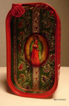 Beautiful shrine with a Lady of Guadalupe - image under a glass cabochon (30x40mm). I make these shrines out of old tin cans, I think that thats great as a framework. They are painted, here in a lighter red with a little glitter, slightly shabby. This shrine is lined with a great green and gold lace with a floral pattern, the inner border decorated with Golden Glitterglue and green satin ribbon. The Madonna under a 30x40mm is framed with red Glitterglue large glass Cabochon. At the top Ive…