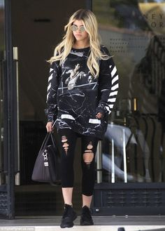 On-trend: The 17-year-oldwore a black baggy marbled crewneck from Off-White featuring a graphic print on the chest and stripes on the sleeves
