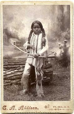 Native American Tribes Clothing Studio portrait from Addison studio, Fort Sill, Oklahoma Territory - child posed in front of painted landscape, in tribal clothing with braids and bow and arrow.