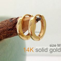 These solid gold medium hoop earrings for men are slightly domed and hugs  the earlobes. 54f3dbf8537e
