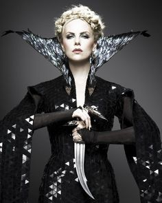 Charlize Theron as the Evil Queen wearing a robe embellished with a feathered collar.